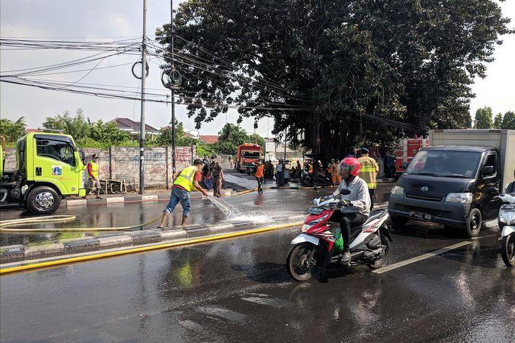 Petugas Sudin Kehutanan Menyemprotkan Air Kejalanan Untuk Menghilangkan Sisa-sisa Gas Air Mata