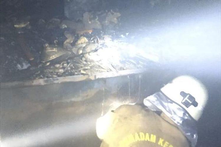 Petugas memadamkan kebakaran yang melalap sebuah toko barang antik di Pasar Rawabening, Jakarta Timur, Jumat (7/6/2019) malam.