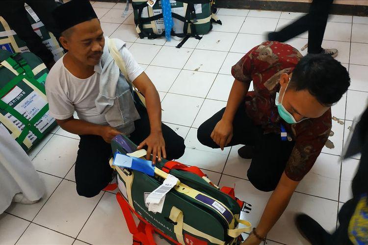 Petugas hendak menggeledah koper jemaah haji yang berisi barang-barang tak sesuai syarat di Asrama Haji Embarkasi Bekasi, Kamis (11/7/2019).