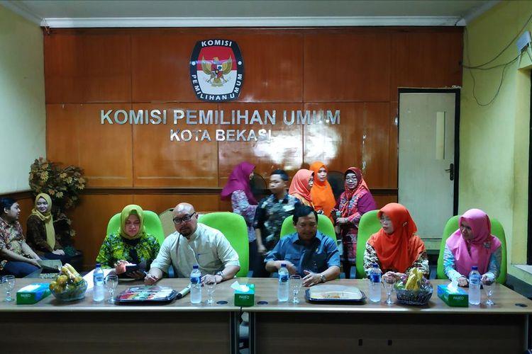 Komisioner KPU RI, Ilham Saputra (tengah-kiri) dan Wakil Ketua Komisi II DPR RI, Herman Khaeron (tengah-kanan) dalam acara penyerahan simbolis biaya santunan kepada 10 keluarga anggota KPPS yang meninggal, di kantor KPU Kota Bekasi, Jumat (12/7/2019).