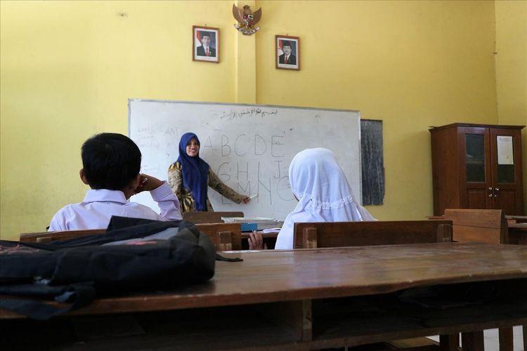 Salah satu guru SDN Sumberaji II, Sriami, membimbing 2 murid barunya, Selaa (16/11/2019). Sekolah dasar itu berada di Dusun Ngapus, Desa Sumberaji, Kecamatan Kabuh, Kabupaten Jombang, Jawa Timur.