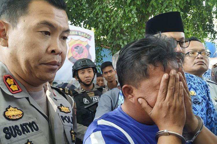 Tersangka ER meutup muka dengan tangan saat konferensi pers di halaman Gedung Juang 45 Sukabumi, Jawa Barat, Rabu (17/7/2019).