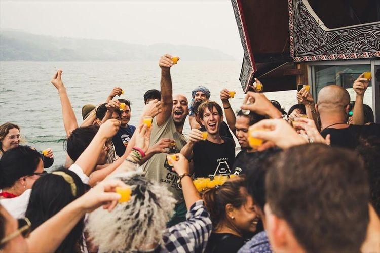 Peserta boat party di event yang digelar Volcano Floating Party menunjukkan minumannya di atas kapal di Danau Toba.
