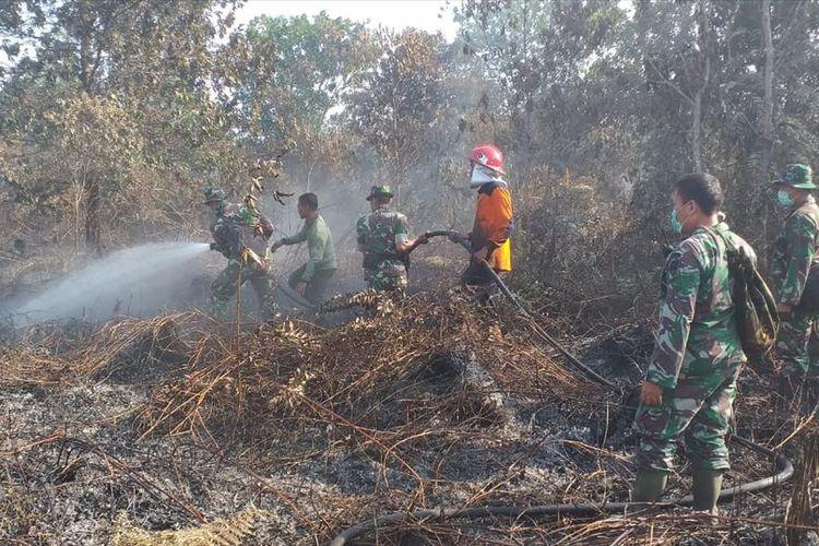 Petugas TNI dan BPBD Pekanbaru memadamkan api karhutla di Kelurahan Air Hitam, Kecamatan Payung Sekaki, Pekanbaru, Riau, Jumat (19/7/2019).