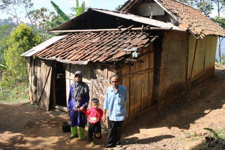 Sati (60), Jodi (7), dan Rakun (70) berdiri di sekitar rumahnya, di dusun pahing RT 1 RW 3, Desa Margabakti Kecamatan Kadugede Kabupaten Kuningan Jawa Barat, Senin (29/7/2019). (MUHAMAD SYAHRI ROMDHON)