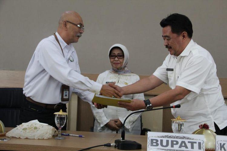 Kepala BPCB Jatim, Andi Muhamad Said (kiri) menyerahkan berkas pendaftaran situs petirtaan kuno di Sumberbeji kepada Kepala Dinas Pendidikan dan Kebudayaan Jombang, Budi Nugroho (kanan), dihadapan Bupati Jombang, Mundjidah Wahab (tengah). Penyerahan berkas dilaksanakan di komplek rumah dinas Bupati Jombang, Rabu (7/8/2019).