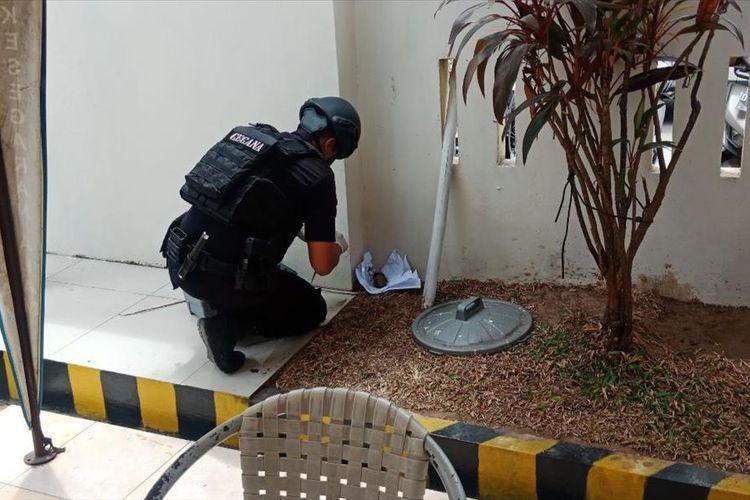 Seorang anggota tim penjinak bom (Jibom) Brimob Polda Sulsel saat mengamankan granat yang ditemukan dua bocah SD di Jalan Teuku Umar 2, Kecamatan Tallo, Makassar, Jumat (9/8/2019).