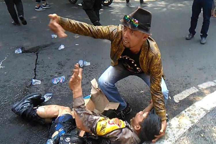Seseorang coba memberikan pertolongan kepada seorang anggota polisi yang terbakar saat terjadi insiden kericuhan dalam aksi unjukrasa di ruas Jalan Siliwangi depan gerbang Pendopo Bupati Cianjur, Jawa Barat, Kamis (15/08/2019) siang(Firman Taufiqurrahman)