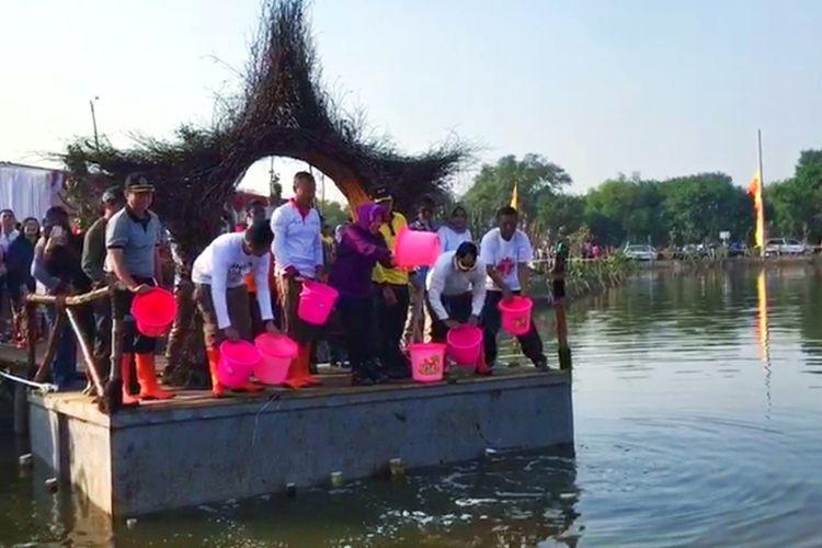Wali Kota Surabaya Tri Rismaharini bersama jajaran Pemkot Surabaya menabur benih ikan di Bozem Medokan Sawah Timur, Gunung Anyar, Surabaya, Jumat (16/8/2019).