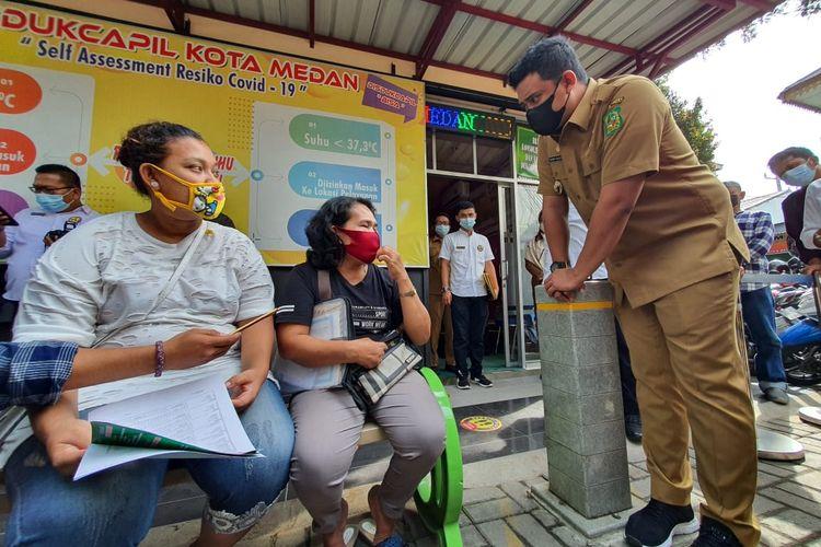 Wali Kota Medan, Bobby Nasution berinteraksi dengan warga yang mengadu kepadanya soal bantuan PKH yang tak kunjung cair, di sela-sela sidak di Disdukcapil Kota Medan, Senin (17/5/2021).