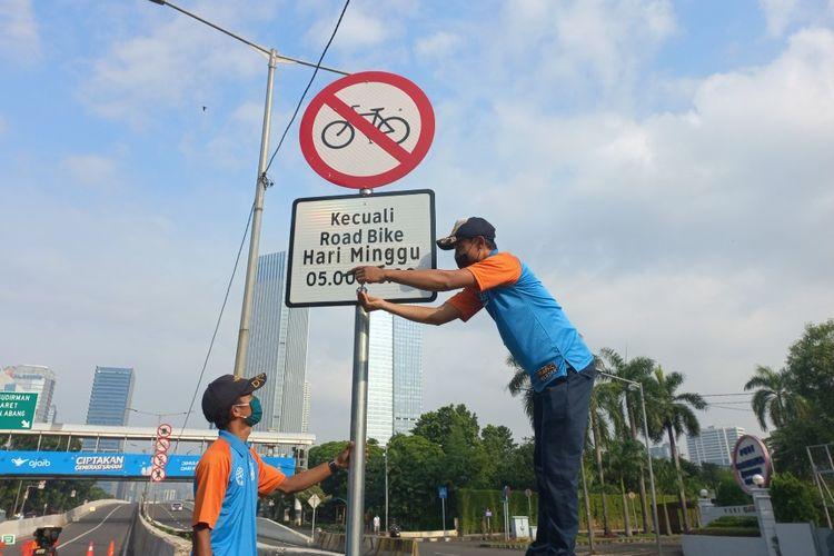 Petugas Dinas Perhubungan DKI Jakarta mencopot rambu larangan sepeda selain road bike melintas di JLNT Kampung Melayu-Tanah Abang, Minggu (13/6/2021).
