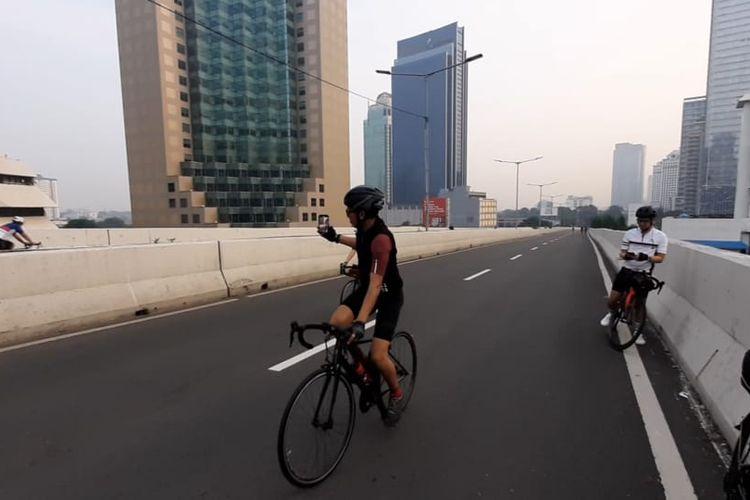 Seorang pesepeda road bike sedang mengambil foto rekannya saat menjajal jalur khusus sepeda di Jalan Layang Non Tol (JLNT) Kampung Melayu-Tanah Abang, Minggu (23/5/2021).