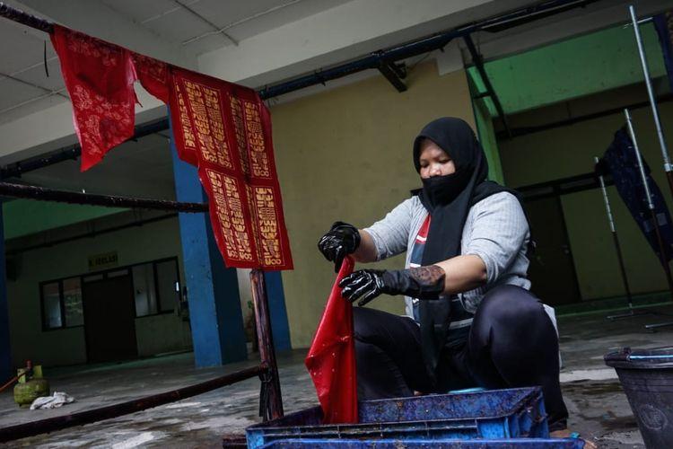 Eni (39), warga Rusun Pulogebang, menunjukkan kain batik tulis yang ia lukis, Jumat (18/6/2021). Eni merupakan salah satu korban gusuran yang kini berjuang memungut kembali sisa-sisa masa kejayaannya sebelum digusur dengan cara aktif terlibat sebagai pengrajin batik.