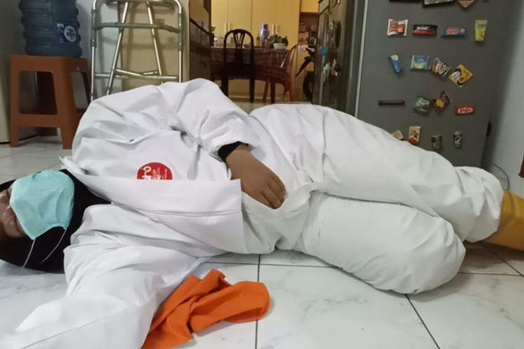 Seorang relawan pemulasaraan jenazah pasien Covid-19 di Pancoran Mas, Depok, Jawa Barat, terkulai kelelahan di rumah duka karena harus mengurusi banyaknya kematian dalam sehari.