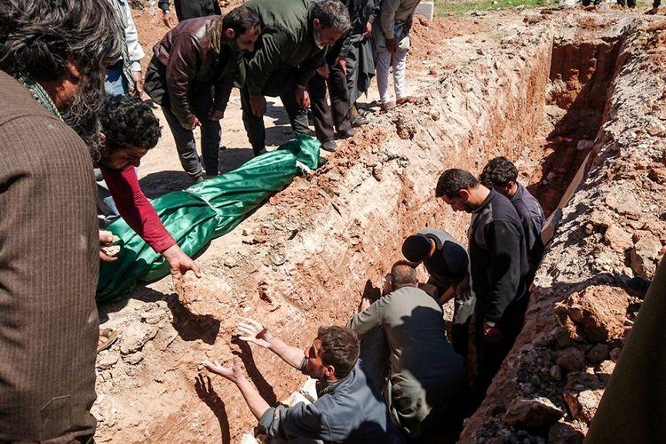 Warga menggali kuburan untuk jenazah korban dari dugaan serangan gas beracun di Khan Sheikhun, kota yang dikuasai kelompok pemberontak di Provinsi Idlib, Suriah barat laut, Rabu (5/4/2017). Sedikitnya 72 orang tewas, termasuk 20 anak-anak akibat serangan senjata kimia tersebut.