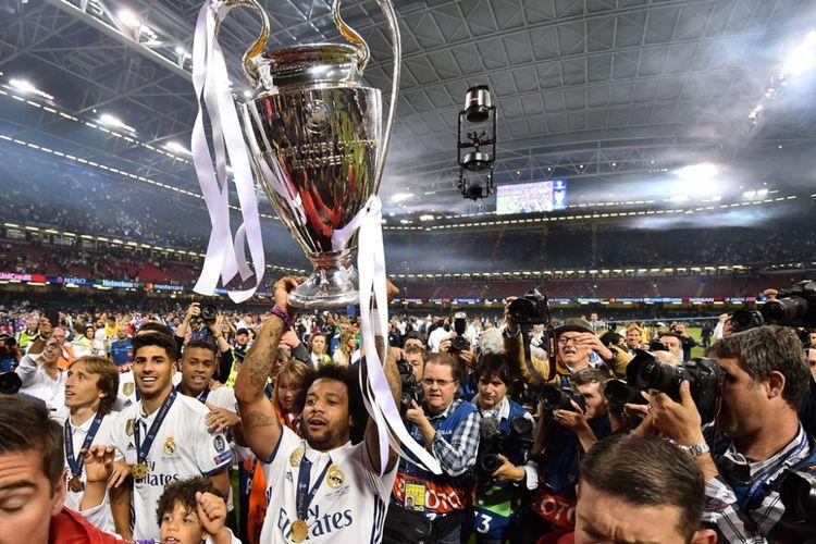 Marcelo mengangkat trofi Liga Champions setelah Real Madrid menang 4-1 atas Juventus pada partai final di Stadion Millenium, Cardiff, Sabtu (3/6/2017).