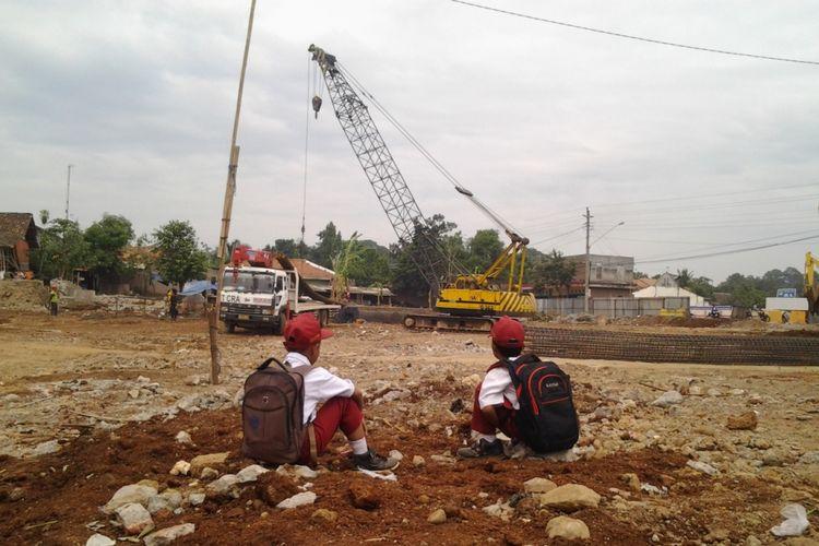 Dua anak SDN 2 Protomulyo Kaliwungu Selatan melihat pengerjaan jalan tol yang berada di belakang sekolahnya.