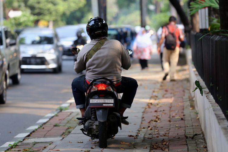 Pengendara sepeda motor yang melintasi trotoar di Jl. H. Agus Salim, Jakarta Pusat, Senin (17/7/2017). Pengendara sering memanfaatkan trotoar untuk memotong jalan agar bisa lebih cepat ketimbang melewati jalan raya.