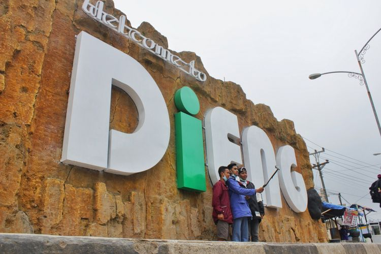 Pengunjung berswafoto di tugu Dieng, Jawa Tengah, Kamis (3/8/2017). Satu hari menjelang perhelatan Dieng Culture Festival 2017, pengunjung mulai memadati kompleks wisata Dieng.