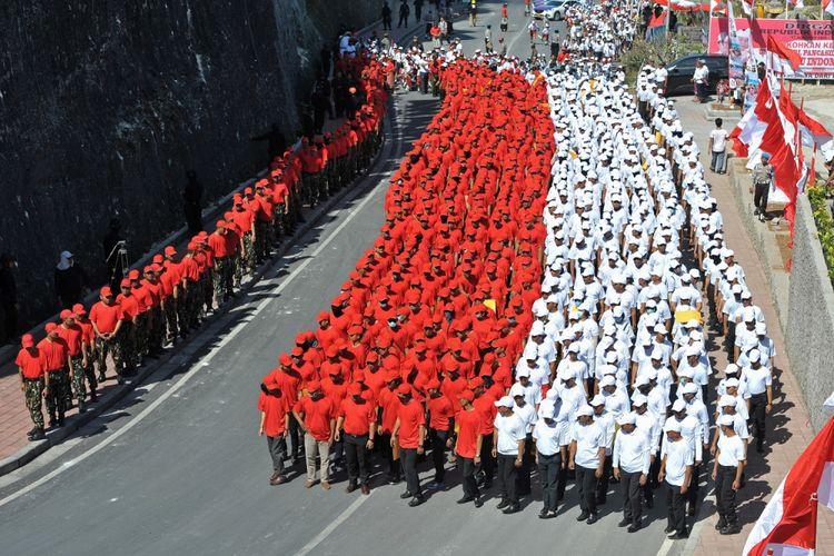 Anggota polisi membentuk formasi merah putih saat pengibaran Bendera Merah Putih terpanjang di Pantai Pandawa, Badung, Bali, Senin (14/8/2017). Pengibaran Bendera Merah Putih sepanjang 800 meter tersebut untuk memperingati HUT ke-72 Proklamasi Kemerdekaan Indonesia, memperkuat nasionalisme dan sekaligus memecahkan rekor MURI. ANTARA FOTO/Nyoman Budhiana/pd/17.