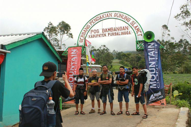 Para pendaki berfoto di bawah gapura sebelum memulai pendakian Gunung Slamet via basecamp Bambangan, Purbalingga, Jawa Tengah, Rabu (16/8/2017)