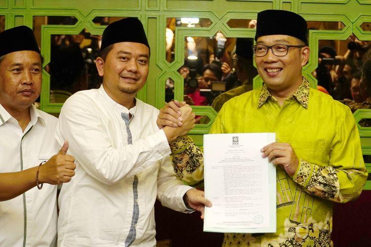 Ketua DPW PKB Jawa Barat Syaiful Huda (tengah) berjabat tangan dengan Wali Kota Bandung Ridwan Kamil (kanan) memberikan memberikan Surat Keputusan Dukungan PKB kepada Ridwan Kamil sebagai Calon Gubernur Jabar, Bandung, Jawa Barat, Senin (11/9). Setelah bergabungnya PKB yang memiliki tujuh kursi di DPRD Jabar, Ridwan Kamil kini memiliki 12 kursi dari partai sebelumnya Nasdem yang memiliki lima kursi, sehingga masih dibutuhkan dukungan sebanyak delapan kursi lagi, agar dirinya dapat diusung menjadi Calon Gubernur Jawa Barat 2018-2023, sesuai dengan syarat yang ditetapkan KPU dengan dukungan minimal 20 persen kursi di DPRD Jabar. ANTARA FOTO/Agus Bebeng/aww/17.
