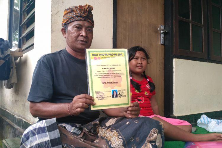 I Gusti Nyoman Putra (52)   dan putrinya Gusti Ayu Vera Noviantari (9)  saat ditemui di kediamaannya, Banjar Bentuyung, Kecamatan Ubud, Gianyar, Bali.