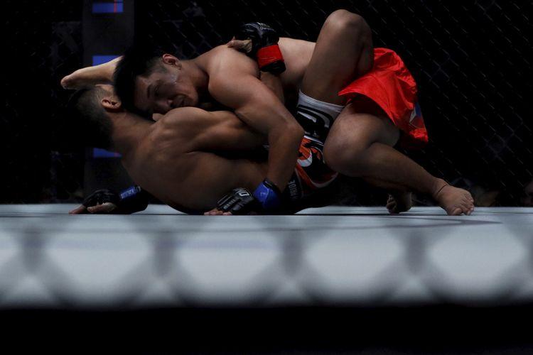 Petarung Geje Eustaquio (atas) bertanding melawan petarung Kairat Akhmetov (bawah) pada pertandingan ONE: Total Victory di Jakarta Convention Center, Sabtu (16/9/2017).