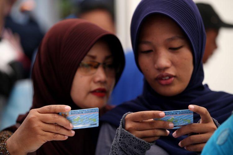Warga mendapatkan e-KTP yang baru dicetak di stan pelayanan dan pencetakan e-KTP di Taman Mini Indonesia Indah (TMII), Jakarta, Jumat (20/10/2017).  Kegiatan yang digelar antara Dinas Kependudukan dan Catatan Sipil DKI bekerja sama dengan Direktorat Jenderal Kependudukan dan Catatan Sipil Kementerian Dalam Negeri ramai diserbu warga yang yang belum memiliki e-KTP.