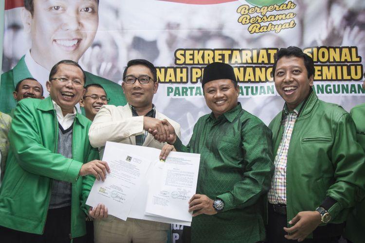 Ketua Umum PPP Romahurmuziy (kanan), Wali Kota Bandung Ridwan Kamil (kedua kiri), Bupati Tasikmalaya Uu Ruzhanul Ulum (kedua kanan), dan Sekjen PPP Arsul Sani (kiri) berfoto bersama sembari menunjukan surat dukungan dari PPP seusai memberikan keterangan pers mengenai pengumuman calon Gubernur dan Wakil Gubernur Jawa Barat, di kantor DPP PPP, Tebet, Jakarta, Selasa (24/10/2017). PPP resmi mengusung Wali Kota Bandung Ridwan Kamil sebagai calon Gubernur dan Bupati Tasikmalaya Uu Ruzhanul Ulum sebagai calon Wakil Gubernur untuk bertarung dalam Pilkada Jawa Barat pada 2018.
