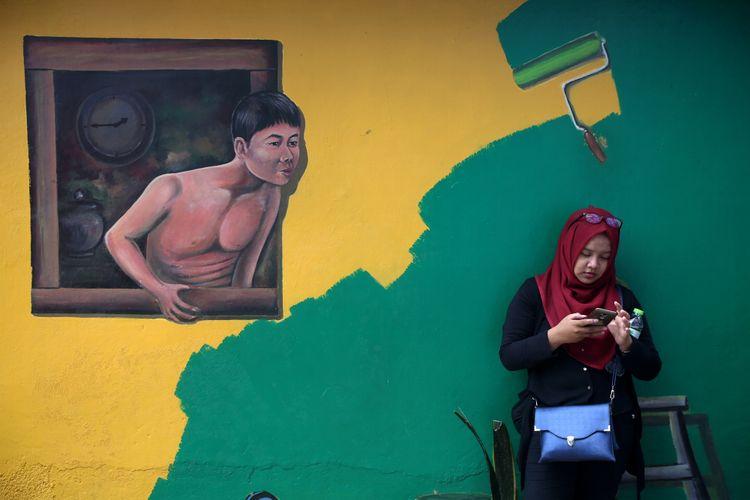 Wisatawan mengunjungi Kampung Warna-warni, Malang, Jawa Timur, Minggu (05/11/2017). Ratusan rumah di tepi Sungai Brantas itu dicat gambar warna-warni untuk menarik wisatawan berkunjung. KOMPAS IMAGES/KRISTIANTO PURNOMO