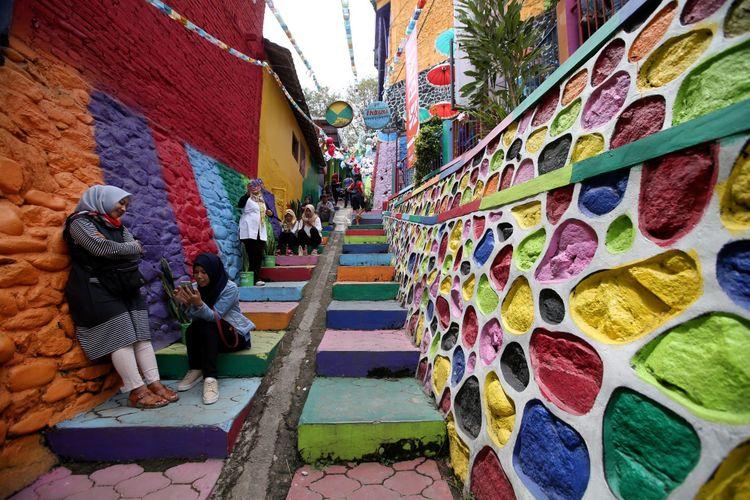 Wisatawan ramai mengunjungi Kampung Warna-warni, Malang, Jawa Timur, Minggu (05/11/2017). Ratusan rumah di tepi Sungai Brantas itu dicat gambar warna-warni untuk menarik wisatawan berkunjung. KOMPAS IMAGES/KRISTIANTO PURNOMO