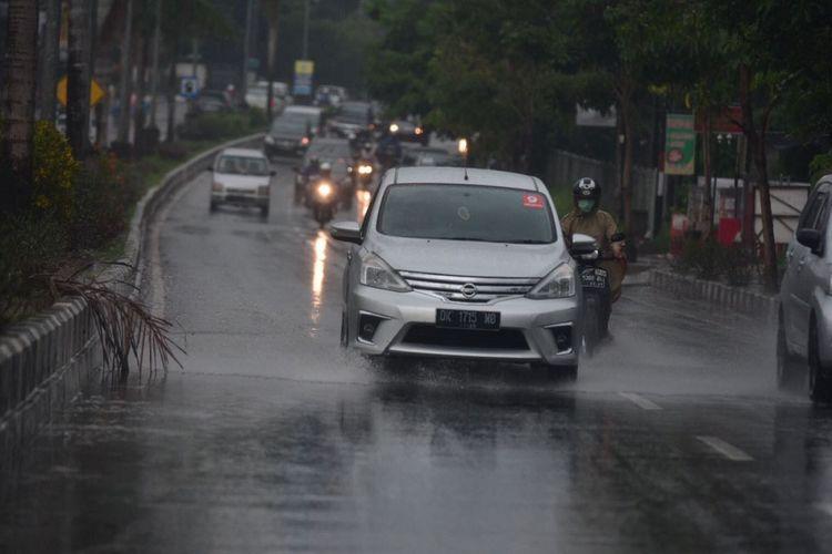 Ilustrasi berkendara diguyur hujan.