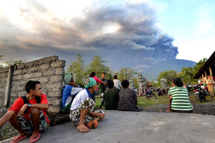 Warga Bali menonton erupsi Gunung Agung terlihat dari Kubu, Karangasem, Bali, 26 November 2017. Gunung Agung terus menyemburkan asap dan abu vulkanik dengan ketinggian yang terus meningkat, mencapai ketinggian 3.000 meter dari puncak. Letusan juga disertai dentuman yang terdengar sampai radius 12 kilometer.