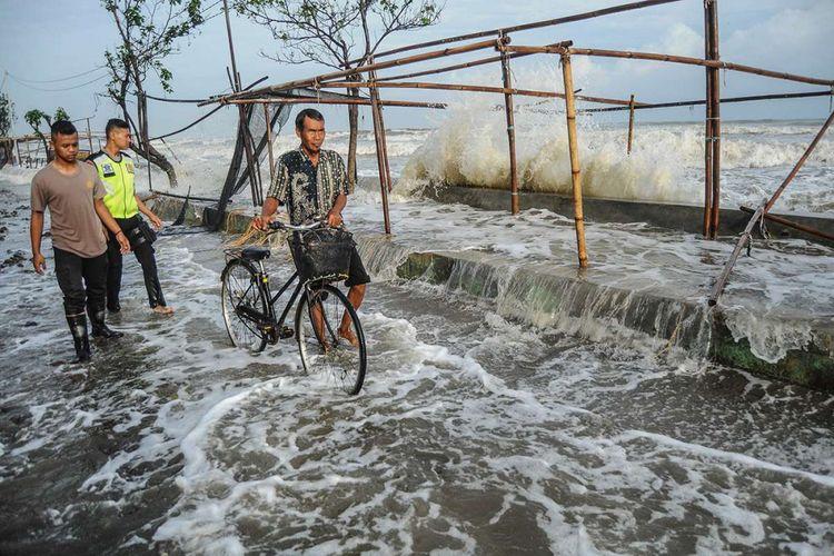 Sejumlah warga menghindari gelombang laut yang mengenai garis pantai di Pantaisari, Pekalongan, Jawa Tengah, Jumat (1/12/2017). Gelombang laut setinggi sekitar 2,5-6 meter dan curah hujan lebat disertai angin kencang yang dipicu siklon tropis Dahlia menyebabkan sejumlah titik di kawasan Pekalongan Utara banjir.