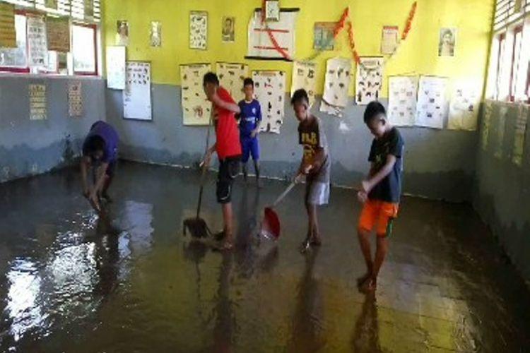 Sejumlah siswa dan guru SDN 18 INP Banua, Majene, Sulawesi Barat, terlihat membersihkan sekolahnya yang terendam banir disertai lumpur. Pasca terendam banjir, sekolah ini diliburkan. Jadwal UAS yang harusnya dilakukan pekan ini pun ditunda hingga kondisi normal.