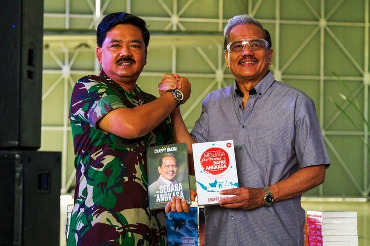 Panglima TNI Marsekal Hadi Tjahjanto (kiri) secara simbolis menerima buku yang diberikan oleh Marsekal TNI (Purn.) Chappy Hakim saat peluncuran buku dan penyerahan 100 buku kepada Angkatan Udara di Skadron Udara 31 Halim Perdanakusuma, Jakarta, Minggu (17/12/2017).