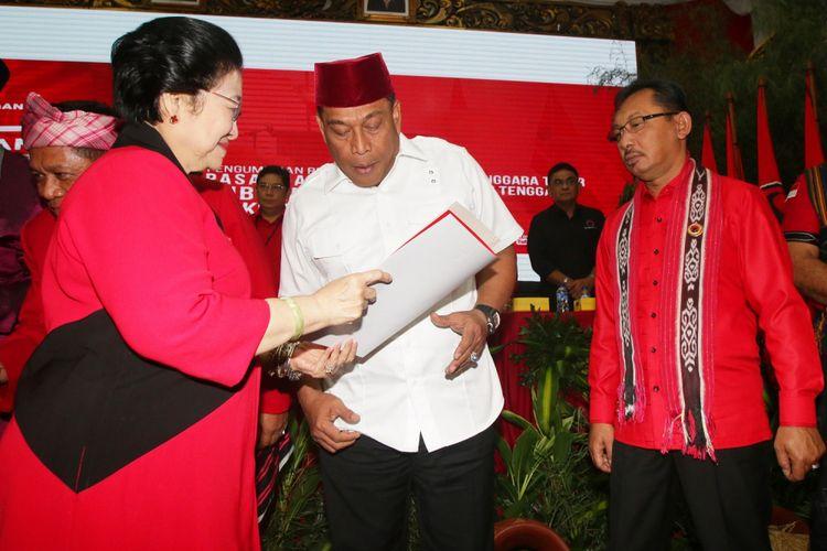 Ketua Umum PDIP Megawati Soekarnoputri (kiri) menyerahkan surat rekomendasi kepada pasangan bakal calon gubernur dan wakil gubernur Maluku Murad Ismail (tengah) dan Barnabas Orno (kanan) seusai mengumumkan bakal calon gubernur dan wakil gubernur empat daerah di DPP PDIP, Jakarta, Minggu (17/12). PDIP resmi mengusung pasangan Arsyadjuliandi Rachman-Suyatno pada Pilgub Riau, Asrun-Hugua pada Pilgub Sulawesi Tenggara, Marianus Sae-Emilia Nomleni pada Pilgub NTT, dan Murad Ismail-Barnabas Orno pada Pilgub Maluku. ANTARA FOTO/Rivan Awal Lingga/ama/17
