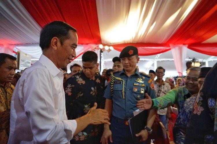 Presiden Joko Widodo bersalaman dengan seorang warga saat penyerahan sertifikat tanah untuk rakyat di Simpang Lima, Semarang, Jawa Tengah, Sabtu (23/12/2017).