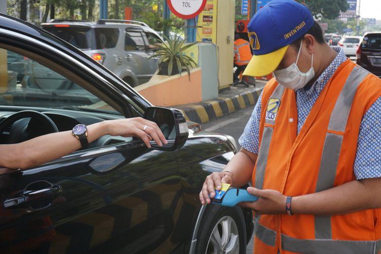 Petugas GT Toll pasteur tengah melayani pengemudi yang hendak masuk ke GT Tol Pasteur, di Bandung, Senin (25/12/2017) dengan alat pembaca uang elektronik portabel.