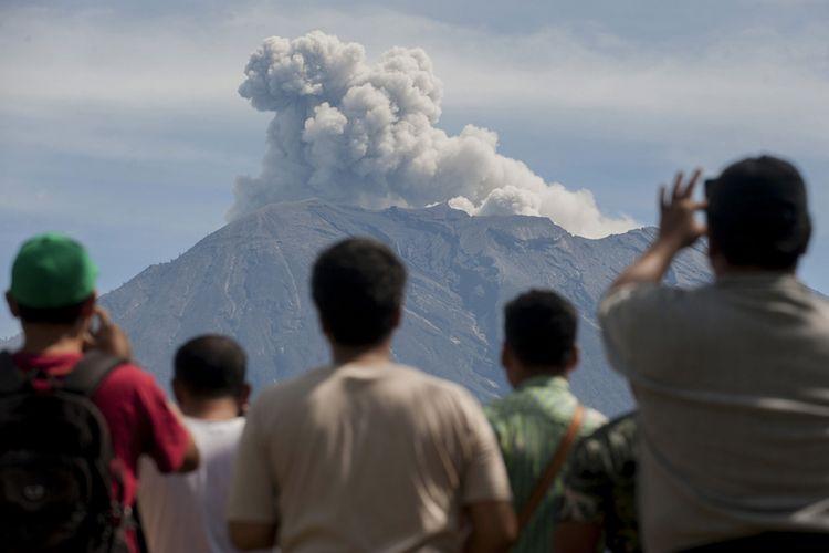 Sejumlah warga menyaksikan asap disertai abu vulkanis keluar dari kawah Gunung Agung yang masih berstatus awas, di Pos Pengamatan Gunung Api Agung, Desa Rendang, Karangasem, Bali, Sabtu (9/12/2017). Pusat Vulkanologi dan Mitigasi Bencana Geologi sejak Jumat lalu mengamati beberapa kali terjadi letusan bersifat efusif sesaat yang disertai hembusan asap dan abu vulkanis hingga ketinggian 2.000 meter dari kawah Gunung Agung.