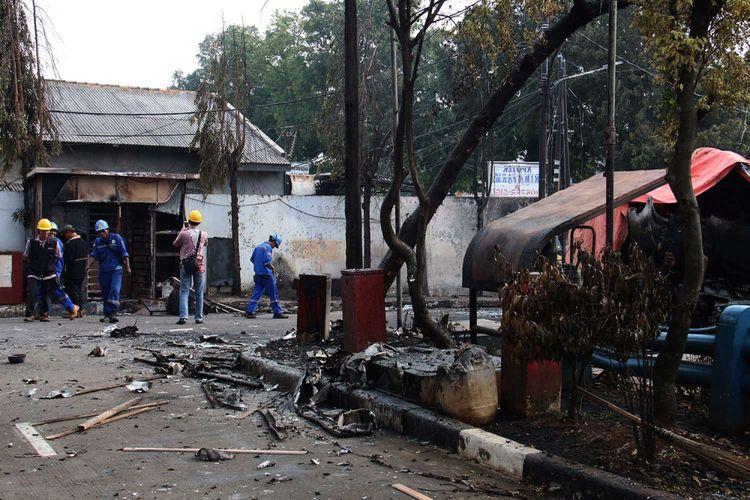 Petugas memeriksa lokasi kejadian terbakarnya truk tangki di SPBU Jalan Kahfi 2, Jagakarsa, Jakarta, Sabtu (30/12/2017). Kebakaran diduga karena ada percikan api saat proses pengisian bensin ke kilang SPBU pada Jumat (29/12/2017), pukul 22.25 WIB.
