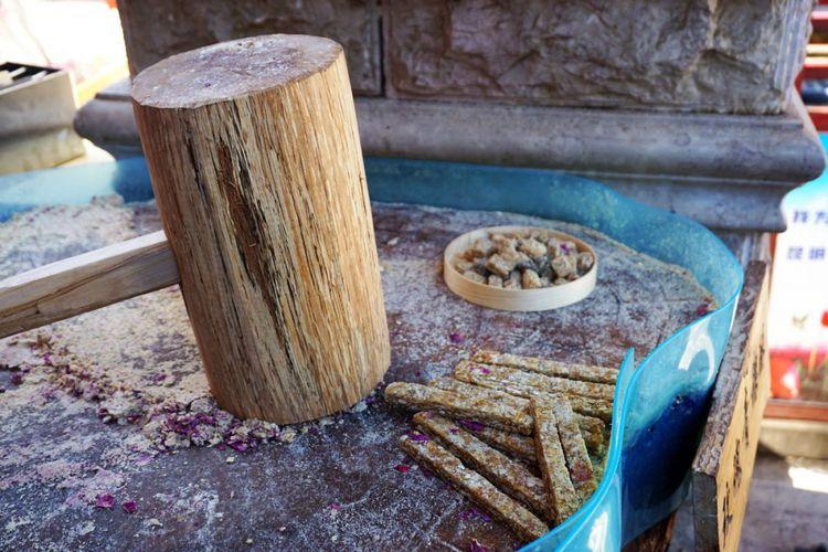 Adonan gula dan kacang dipukul di atas gelondong kayu di sebuah toko di Yunnan Ethnic Village.