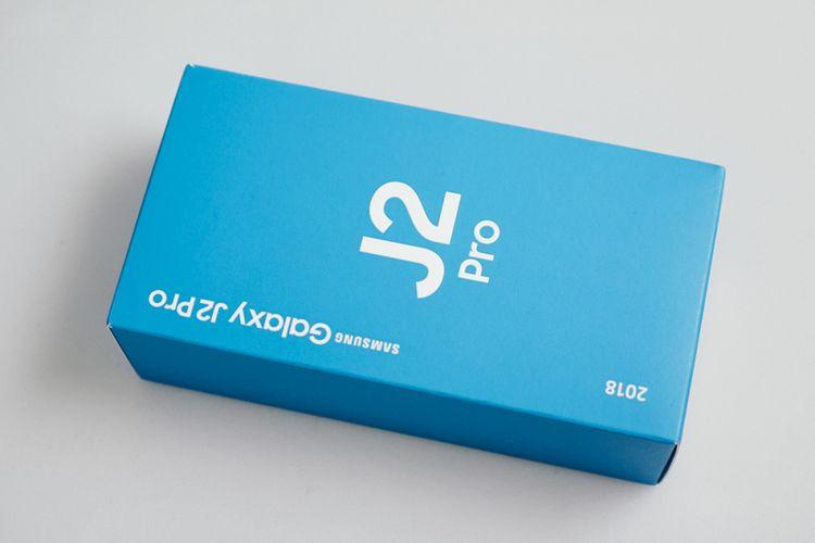 Kotak kemasan Galaxy J2 Pro (2018) nyaris seluruhnya berwarna biru khas Samsung. Nama perangkat tertera di bagian depan dengan tulisan putih berukuran besar.