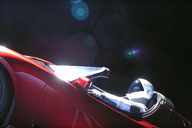 Gambar yang diambil dari video livestream ini menunjukkan manekin bernama Starman duduk di mobil sport Tesla milik Elon Musk yang dibawa roket Falcon Heavy melintasi luar angkasa, Selasa (6/2/2018) waktu setempat. Roket yang diklaim paling kuat di dunia itu memiliki tenaga pendorong setara dengan 18 pesawat Boeing 747, dan diketahui mampu mengirim muatan berat seperti satelit untuk pemerintah dan berbagai perusahaan swasta.