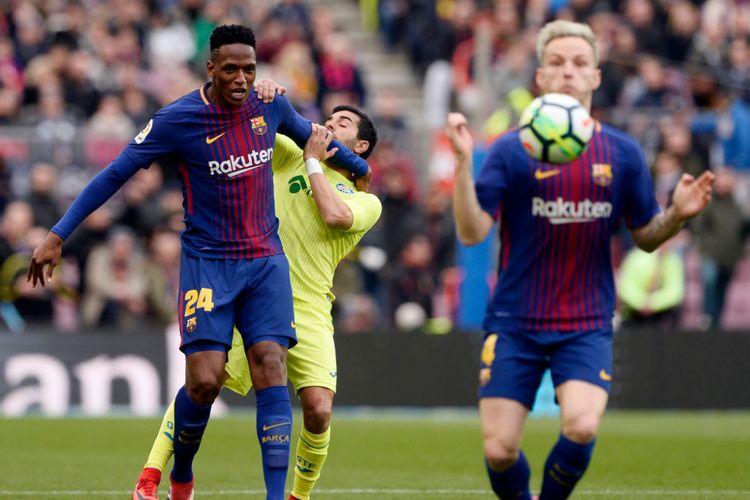 Yerry Mina menahan laju Angel Rodriguez saat hendak mengejar bola yang berada dalam penguasaan Ivan Rakitic pada pertandingan La Liga antara Barcelona dan Getafe di Camp Nou, Minggu (11/2/2018).