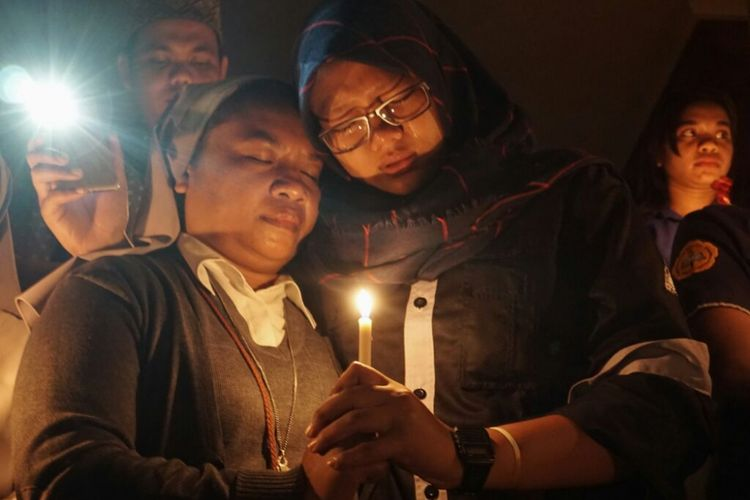 Jari Suster Lili dan jari Olivia Prisandra menyatu mengengam sebuah lilin yang menyala saat mengikuti acara doa lintas iman di depan Auditorium Driyarkara Universitas Sanata Dharma (USD),Yogyakarta.