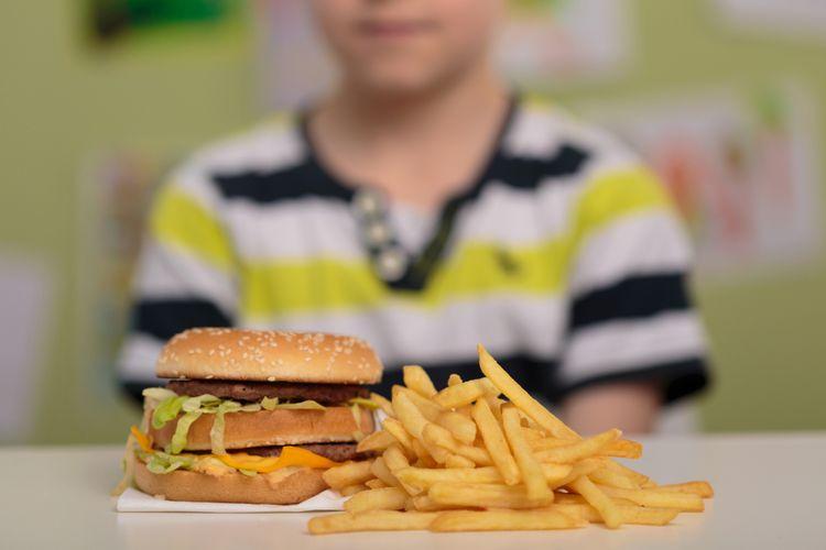 Ilustrasi anak dengan burger dan kentang goreng