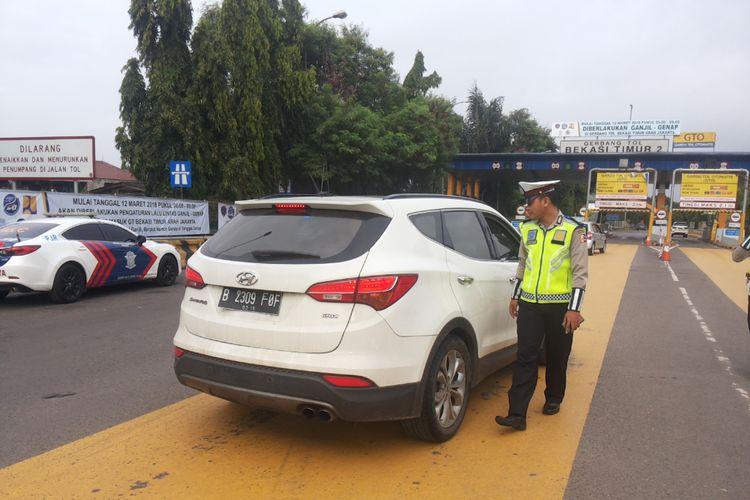 Salah satu mobil berpelat ganjil yang diminta putar balik di depan gerbang tol Bekasi Timur arah Jakarta pada hari pertama penerapan skema ganjil genap Tol Cikampek, Senin (12/3/2018).