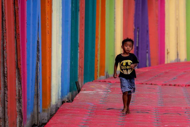 Anak-anak bermain di tepian Danau Sunter di wilayah Kelurahan Sunter Jaya, Kecamatan Tanjung Priok, Jakarta Utara, Minggu (25/3/2018). Pemprov DKI Jakarta melakukan program pengecatan kampung warna-warni di kawasan Danau Sunter untuk memperindah lingkungan sekaligus guna mengubah kesan kumuh kawasan tersebut.